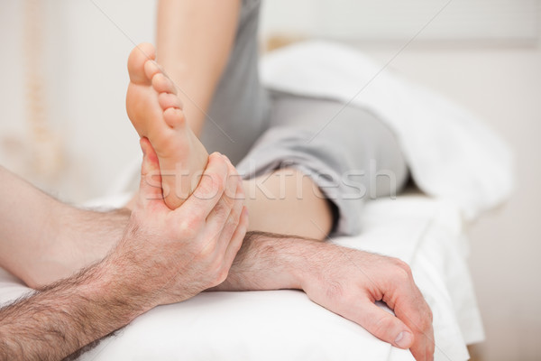 Woman having a foot massage while bending a leg in a medical room Stock photo © wavebreak_media