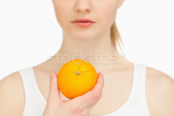 Woman holding an orange against white background Stock photo © wavebreak_media