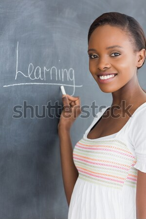 Black woman holding a chalk next to a blackboard in a classroom Stock photo © wavebreak_media