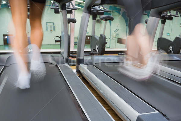 Two people running on treadmills side by side in the gym Stock photo © wavebreak_media