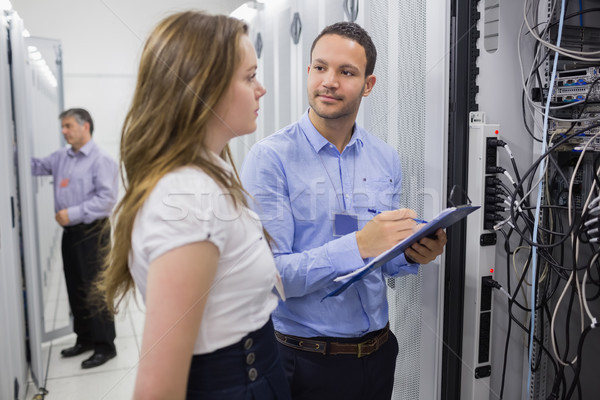 Two people checking servers with one holding clipboard in data center Stock photo © wavebreak_media