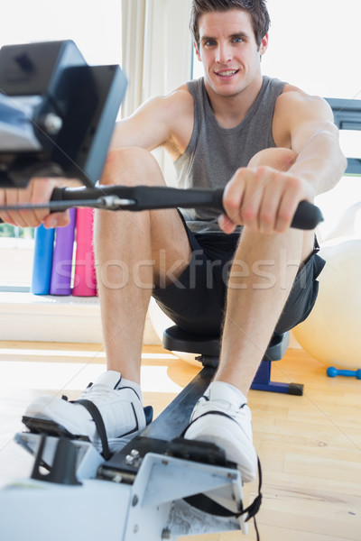 Man working out on row machine in fitness studio Stock photo © wavebreak_media
