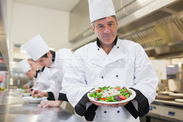 Cheerful chef presenting his salad with others preparing salads in kitchen Stock photo © wavebreak_media