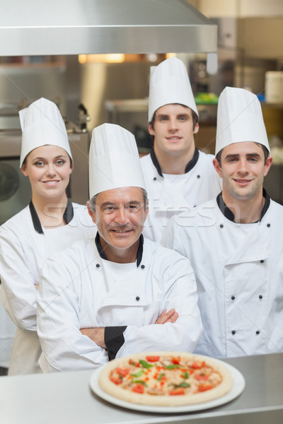Smiling group of Chef's with a pizza on the counter Stock photo © wavebreak_media