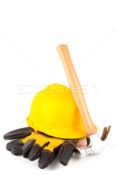Hammer leaning against hard hat and builder's gloves on white background Stock photo © wavebreak_media
