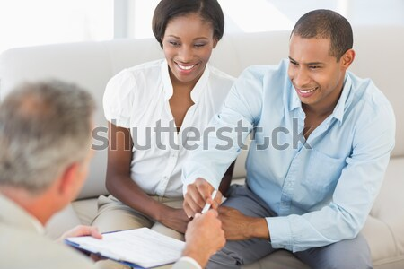 Young smiling couple signing contract on the couch Stock photo © wavebreak_media