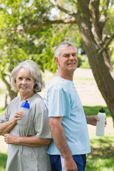 Mature couple standing with water bottles at park Stock photo © wavebreak_media