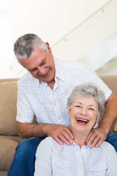Man giving his senior wife a shoulder rub who is smiling at came Stock photo © wavebreak_media