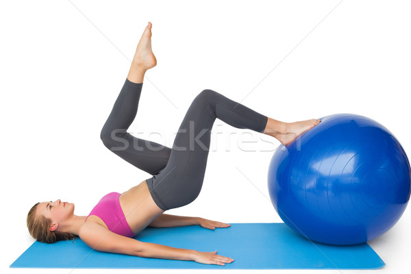 Stock photo: Side view of a fit woman exercising with fitness ball