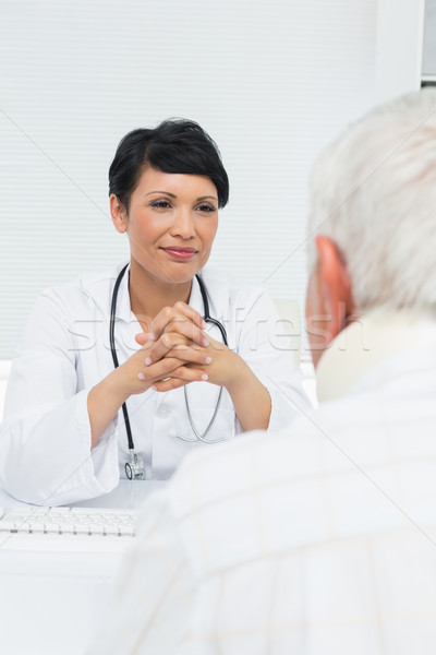 Young female doctor attentively listening to senior patient Stock photo © wavebreak_media