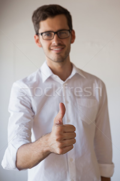 Casual businessman giving thumbs up to camera Stock photo © wavebreak_media