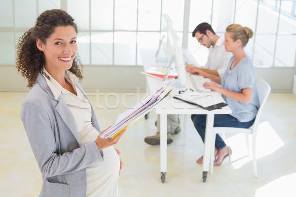 Enceintes femme d'affaires souriant caméra équipe derrière Photo stock © wavebreak_media