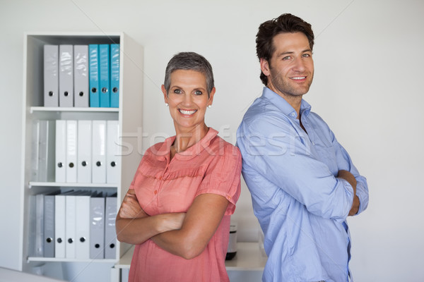 Casual smiling business team standing back-to-back Stock photo © wavebreak_media