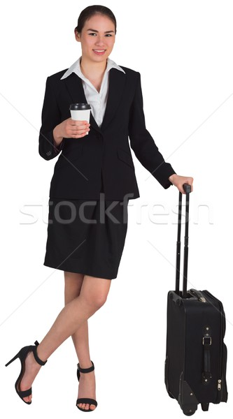 Businesswoman leaning on her suitcase holding coffee Stock photo © wavebreak_media