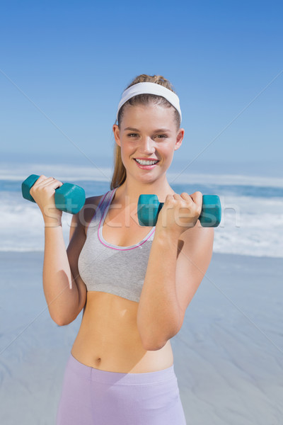 Sporty happy blonde lifting dumbbells on the beach  Stock photo © wavebreak_media