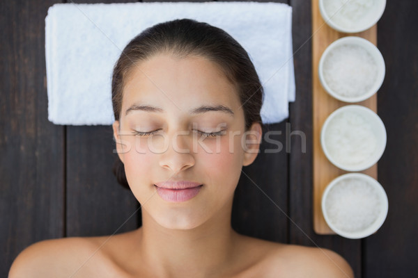 Peaceful brunette lying on towel with treatments beside her Stock photo © wavebreak_media