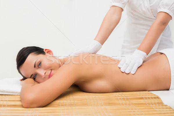 Stock photo: Beautiful brunette enjoying an exfoliating back massage smiling