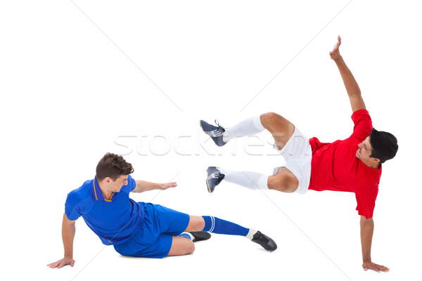 Stock photo: Football players tackling for the ball