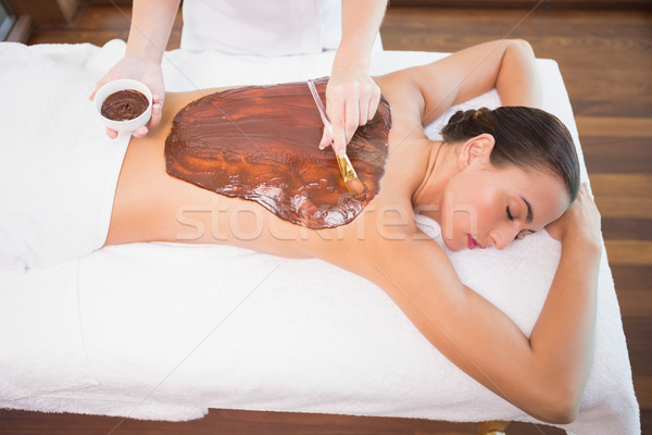 Stock photo: Attractive woman receiving chocolate back mask at spa center