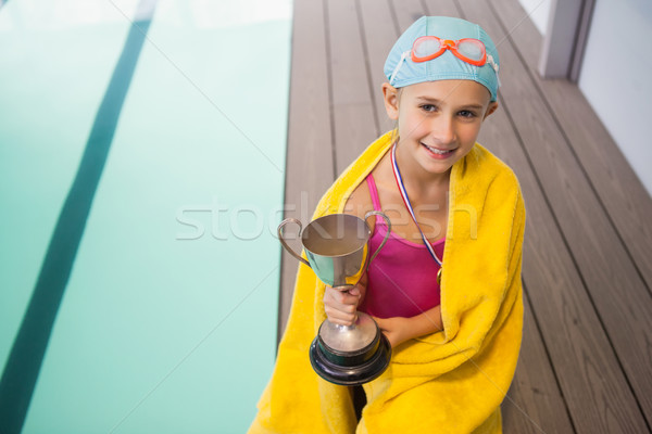 Cute little girl sitting poolside wrapped in towel Stock photo © wavebreak_media
