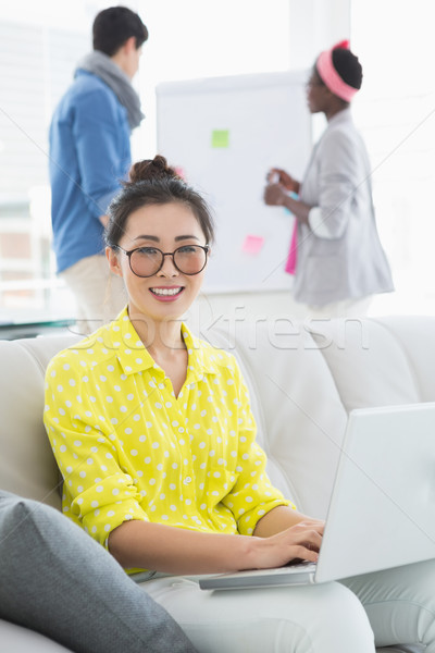 Stock photo: Young creative woman using laptop on couch