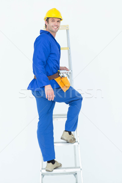 Portrait of repairman climbing step ladder Stock photo © wavebreak_media
