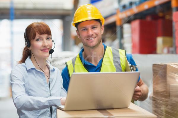 Sorridere imprenditrice indossare auricolare utilizzando il computer portatile magazzino Foto d'archivio © wavebreak_media
