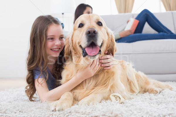 Girl embracing Golden Retriever while lying on rug Stock photo © wavebreak_media