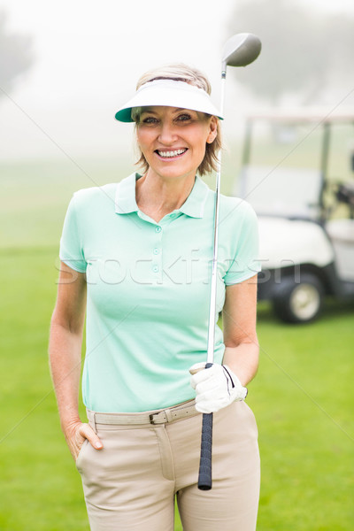 Stock photo: Happy golfer with golf buggy behind