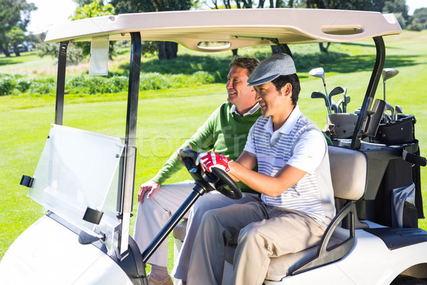 Golfing friends laughing together in their golf buggy Stock photo © wavebreak_media