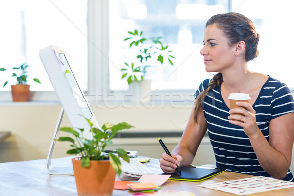 Smiling casual businesswoman working on digitizer and holding co Stock photo © wavebreak_media