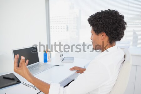 Tired casual businesswoman sitting at desk Stock photo © wavebreak_media
