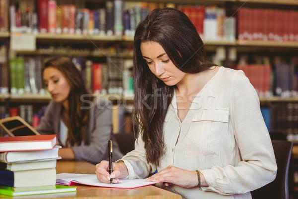 Ziemlich Brünette Studenten schriftlich Merkzettel Bibliothek Stock foto © wavebreak_media