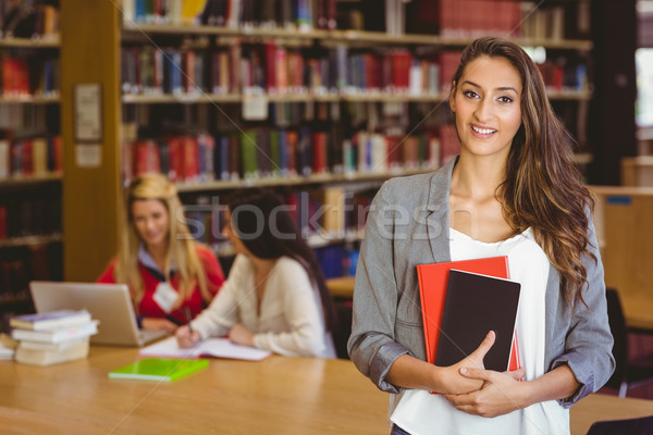 Pretty student holding books with classmates behind her Stock photo © wavebreak_media