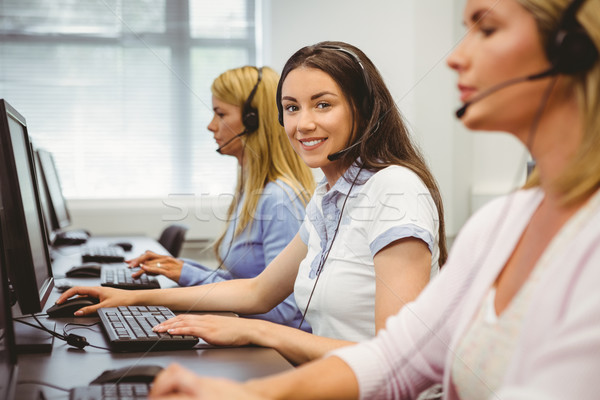 Smiling call centre agent talking on the headset Stock photo © wavebreak_media