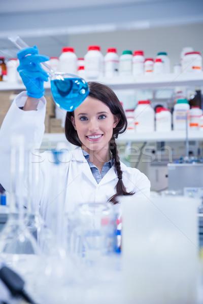 Chemist raising beaker of blue liquid Stock photo © wavebreak_media