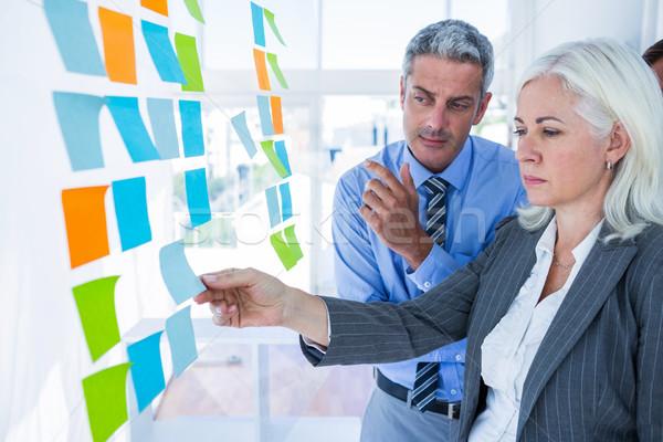 Pessoas de negócios olhando postá-lo parede escritório homem Foto stock © wavebreak_media
