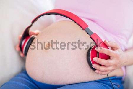 Terhes nő fejhallgató has otthon nappali ház Stock fotó © wavebreak_media