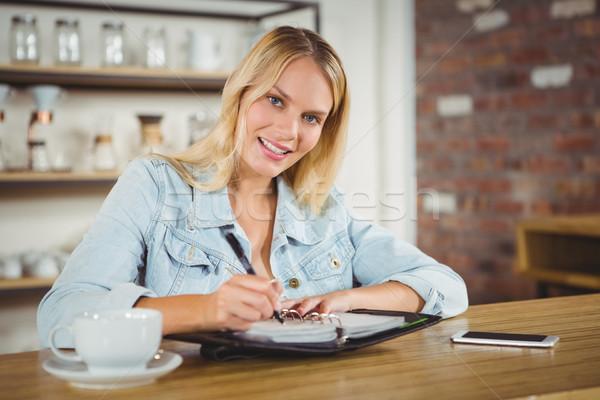 Smiling blonde having coffee and writing in planner Stock photo © wavebreak_media