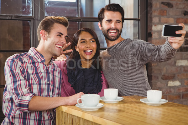 Groupe amis regarder smartphone café affaires Photo stock © wavebreak_media