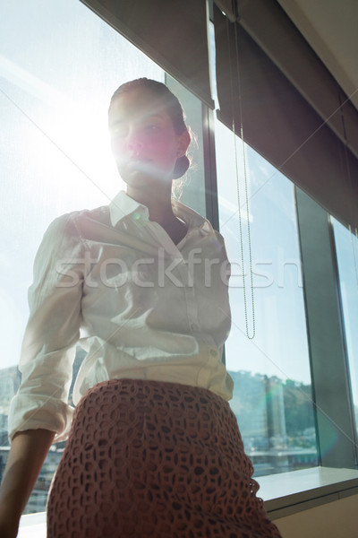 Thoughtful businesswoman standing by brightly lit window in office Stock photo © wavebreak_media