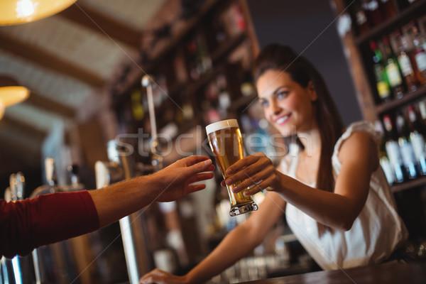 Female bar tender giving glass of beer to customer Stock photo © wavebreak_media