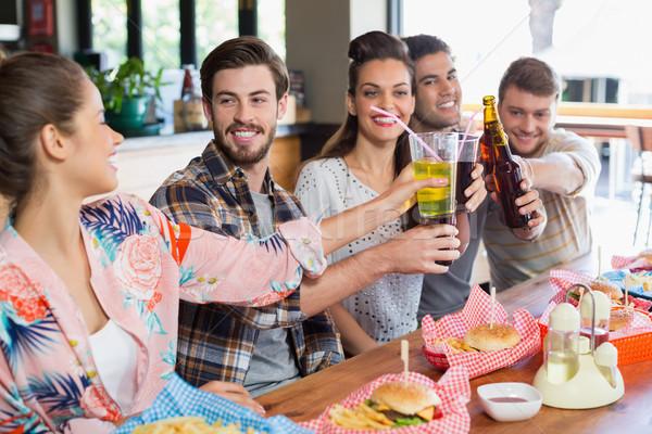 Cheerful friends enjoying beer with food at restaurant Stock photo © wavebreak_media