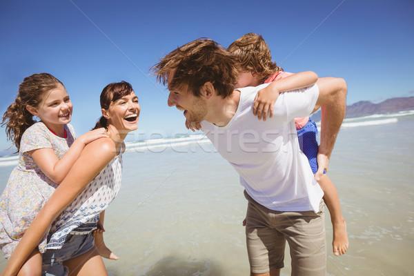 Cheerful parents piggybacking their children at beach Stock photo © wavebreak_media
