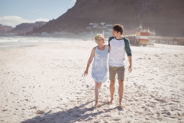 Young man with his mother walking on sand at beach Stock photo © wavebreak_media