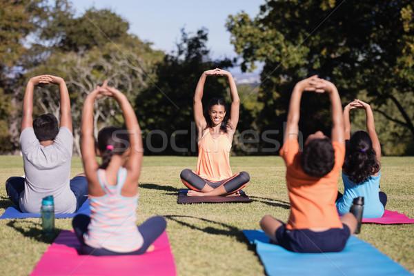 Happy instructor teaching children stretching while sitting on mat Stock photo © wavebreak_media
