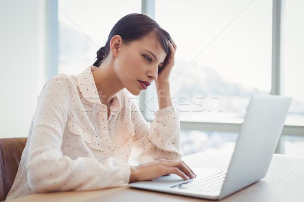 Tensed executive using laptop at desk Stock photo © wavebreak_media