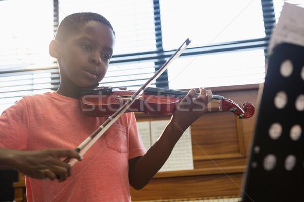 Boy playing violin while sitting in classroom Stock photo © wavebreak_media