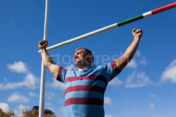Low angle view of smiling rugby player with arms raised against blue sky Stock photo © wavebreak_media