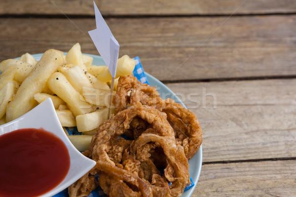 лука кольца картофель фри кетчуп пластина деревянный стол Сток-фото © wavebreak_media